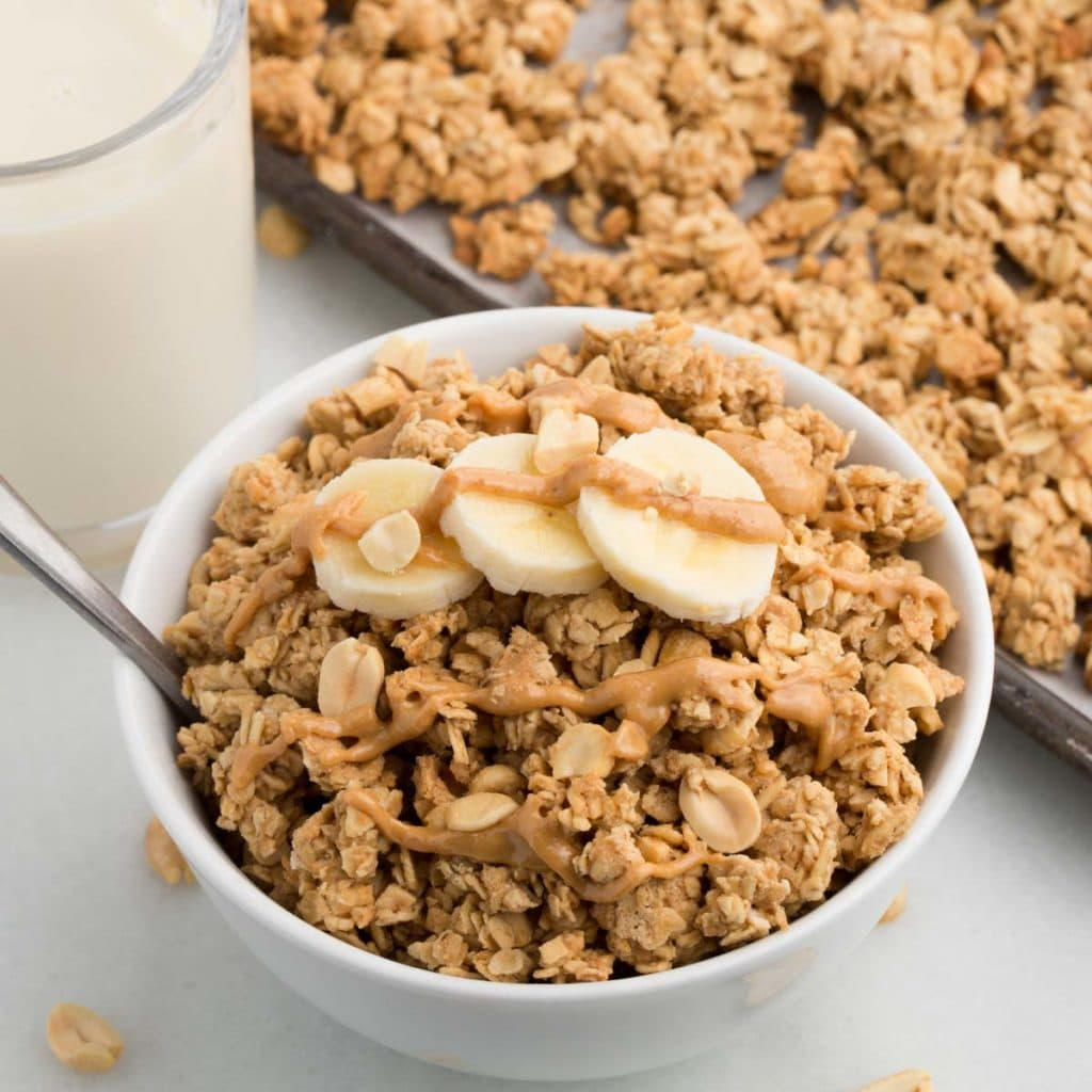 peanut butter granola in white bowl topped with sliced bananas and line of peanut butter