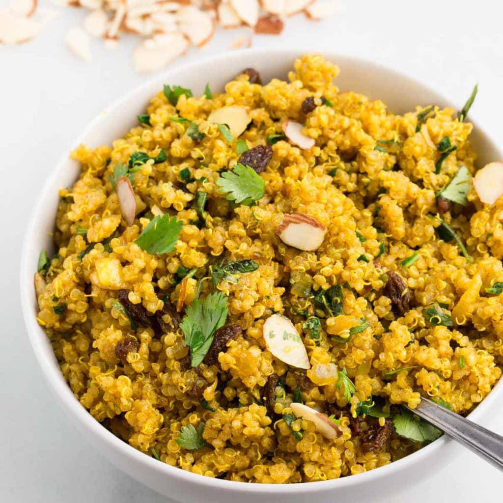 vegan curried quinoa in white bowl with white background