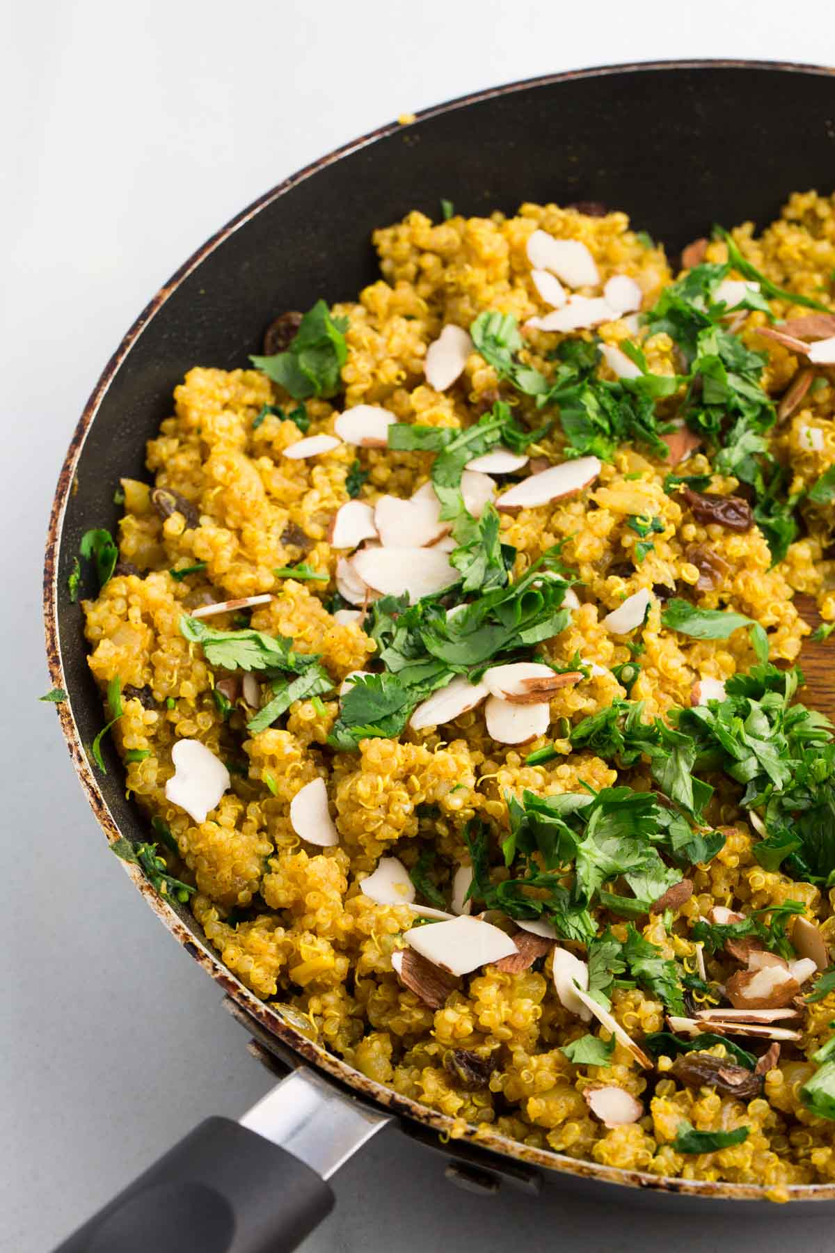 vegan curried quinoa garnished with cilantro and almonds in skillet with white background