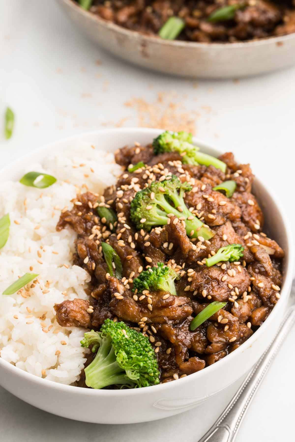 Vegan beef and broccoli with white rice in white bowl with white background