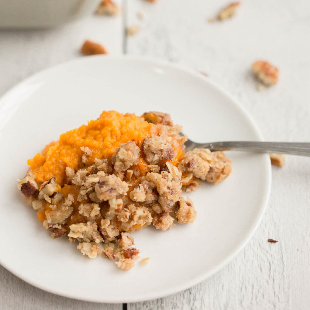 vegan sweet potato casserole on white plate with white wooden background