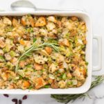 vegan stuffing in white and gray baking dish garnished with rosemary