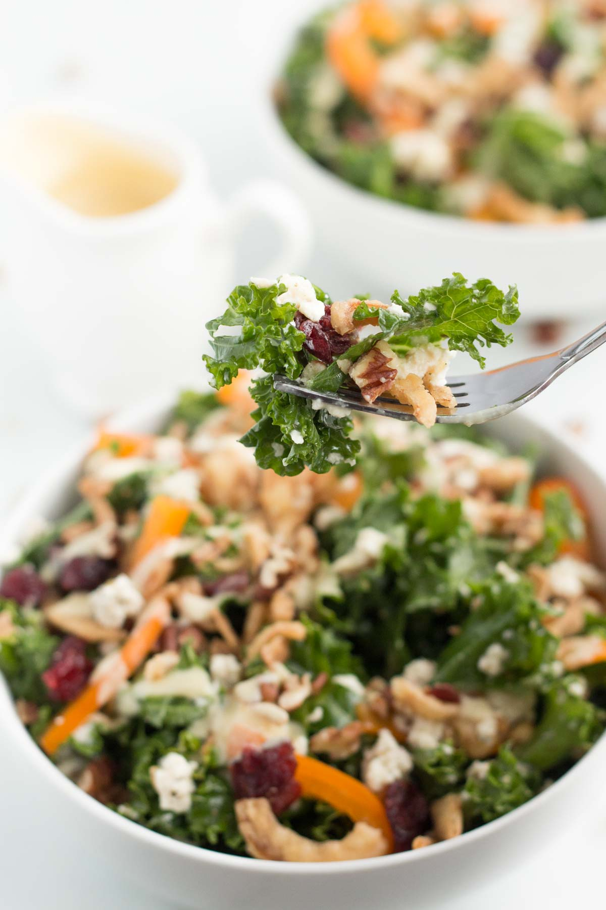forkful of cranberry pecan kale salad with white salad bowls in background