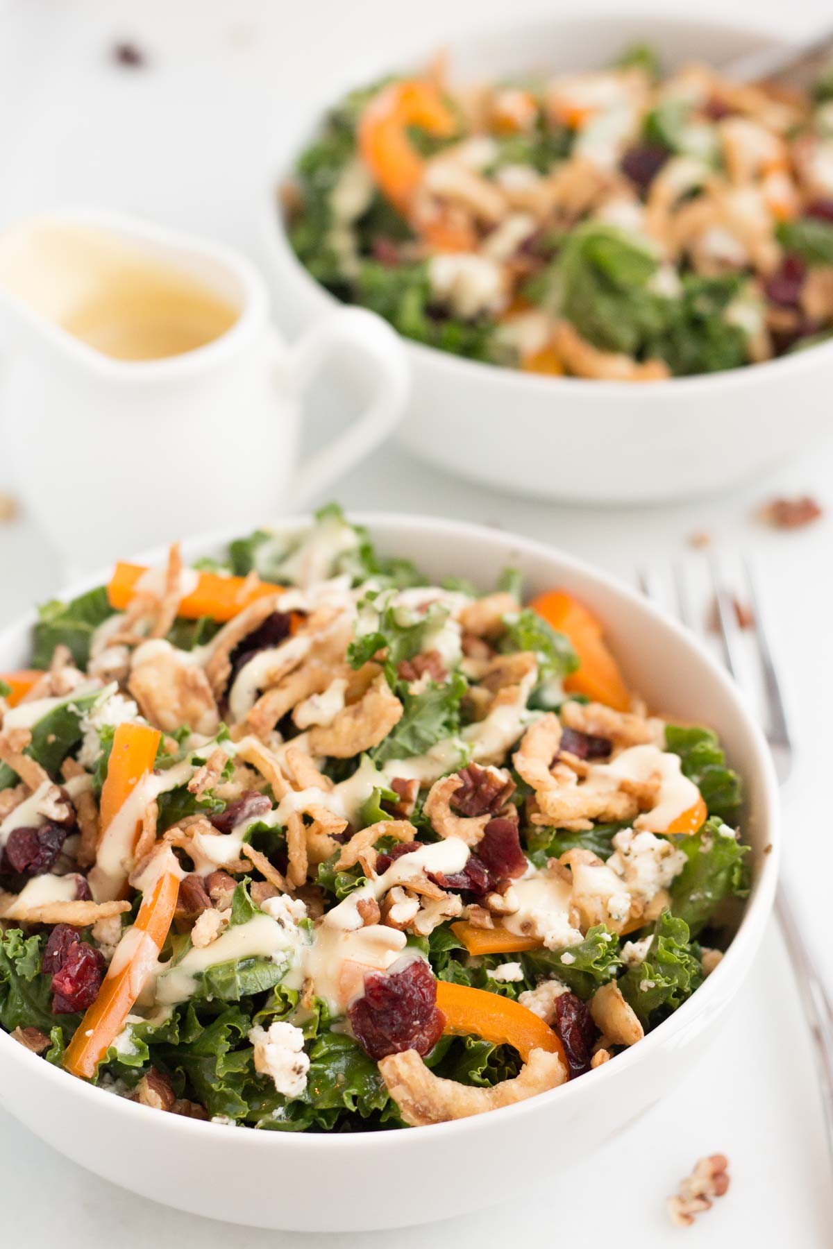 cranberry pecan kale salad in white bowl with white background