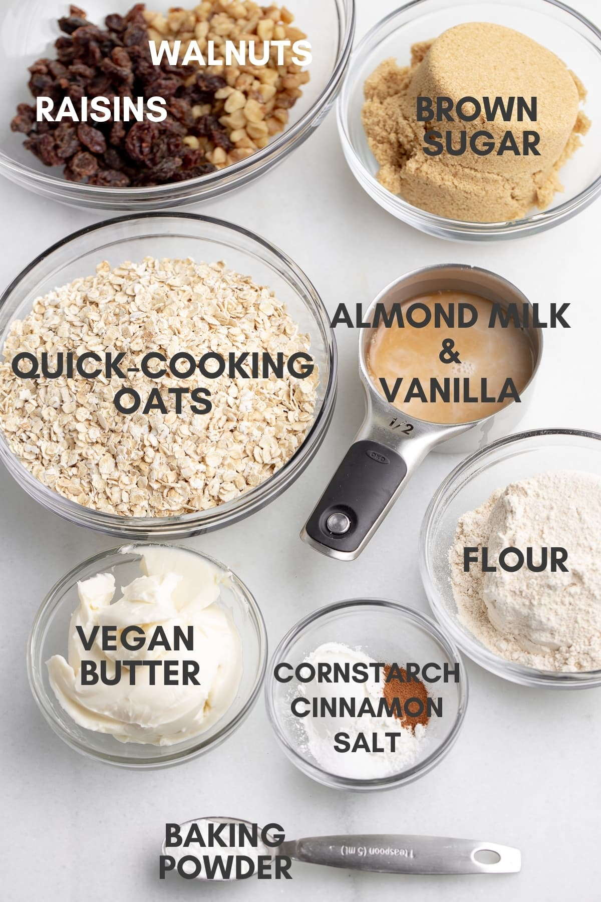 ingredients for vegan oatmeal cookies assembled in small glass bowls and metal measuring spoons with white marble background