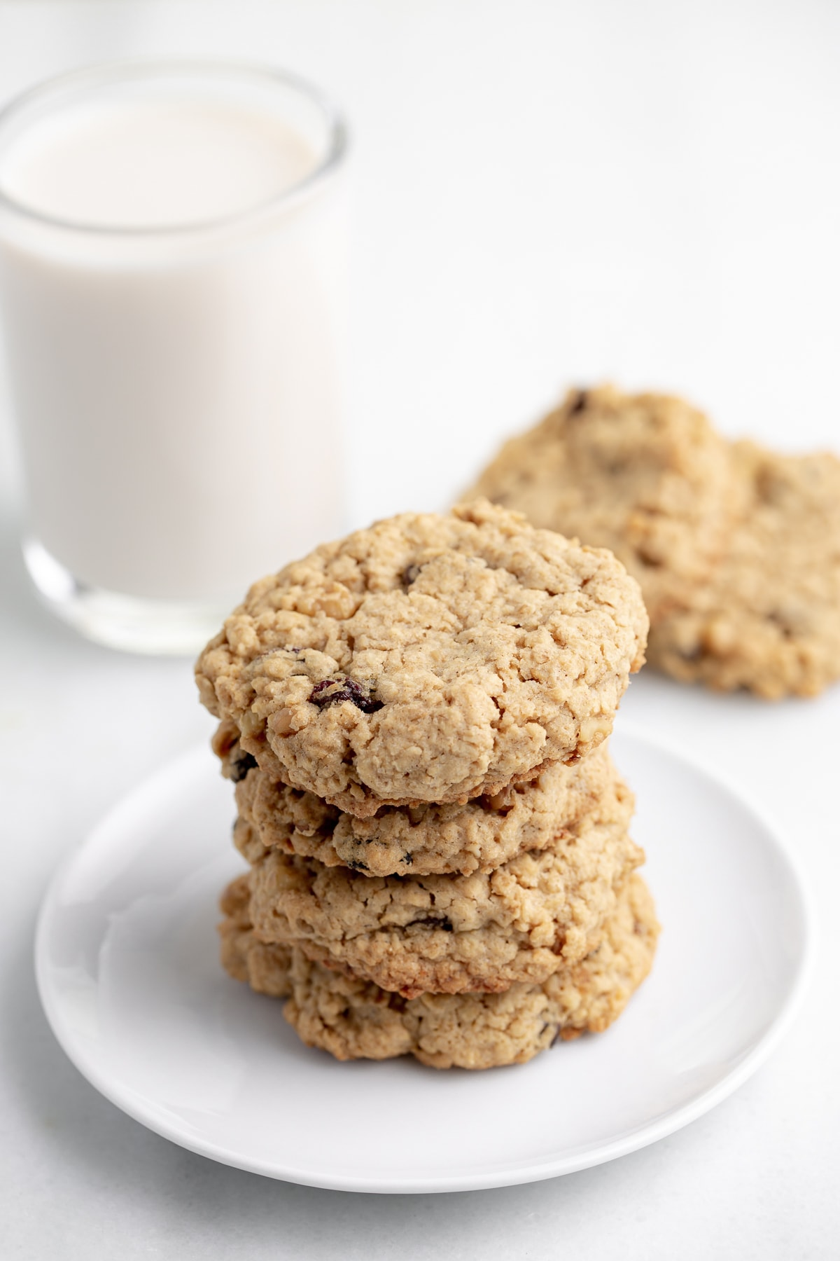 stack of 5 vegan oatmeal cookies on white plate with glass of nondairy milk and white marble background