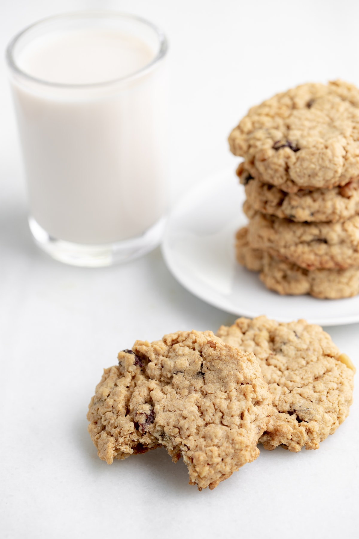 vegan oatmeal cookies with bite taken out of one on white marble background